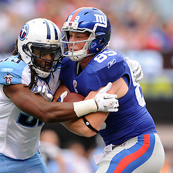 Tight End Kevin Boss #89 of the New York Giants is wrapped up by free safety Michael Griffin of the Tennessee Titans after a reception during first half NFL football action between the New York Giants and Tennessee Titans at New Meadowlands Stadium in East Rutherford, New Jersey. The game is tied at half time.