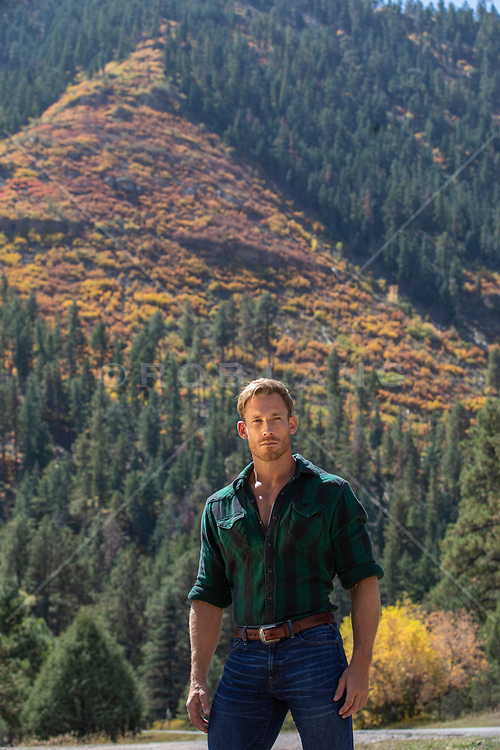 hot man outdoors in Fall by a colorful mountain