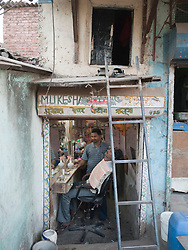Barber shop with barber's accomodation above, man being shaved, Mumbai.