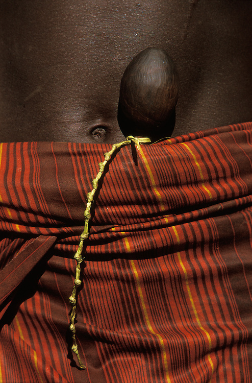 Tucked into his loincloth a young Hamar carries a boko, a phallic symbol showing that he will soon perform the bull jump, a ritual making him eligible to marry, in South Omo, Ethiopia. The knots on the string mark the number of days until the young man's jump. The 40,000-strong, cattle-herding Hamar are among the largest of the 20 or so ethnic groups which inhabit the culturally diverse Omo region in south-west Ethiopia.