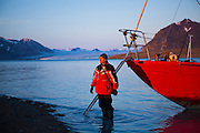 Zbigniew Nawrot steps off the Eltanin, anchored in Josephbukta, and onto dry ground to visit a research outpost in Calypsobyen, Svalbard. The yacht travels from Poland to Svalbard every summer to provide transportation to researchers and tourists. Recherchebreen is visible in the distance.