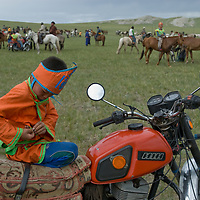 A youngster relaxes on his father's motorcycle after riding bareback in a 20km horse race at a naadam festival on a remote pass near Muren, Mongolia. These Russian and Chinese made machines are a sign of rapid modernization in Mongolia's ancient nomadic culture.