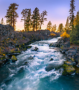 The waters of the Deschutes River cascade through a lava rock channel at Dillon Falls as the last light of day warms the autumn hued foliage along the riverbank.