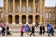 """21 NOVEMBER 2020 - DES MOINES, IOWA: People walk past the front of the Iowa State Capitol before a """"Stop the Steal"""" rally in Des Moines. About 100 supporters of US President Donald Trump gathered at the Iowa State Capitol to rally in support of the President and in opposition to the outcome of the US election. They are a part of the """"Stop the Steal"""" movement which has spread across the US. This is the third week that there have been """"Stop the Steal"""" rallies across the US. Most independent observers and election officials, both Republican and Democratic, have said the election was free and fair and that there was no election fraud.    PHOTO BY JACK KURTZ"""