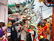 """23 JUNE 2015 - MAHACHAI, SAMUT SAKHON, THAILAND: Chinese dragon dancers perform during the City Pillar Shrine procession in Mahachai. The Chaopho Lak Mueang Procession (City Pillar Shrine Procession) is a religious festival that takes place in June in front of city hall in Mahachai. The """"Chaopho Lak Mueang"""" is  placed on a fishing boat and taken across the Tha Chin River from Talat Maha Chai to Tha Chalom in the area of Wat Suwannaram and then paraded through the community before returning to the temple in Mahachai.   PHOTO BY JACK KURTZ"""