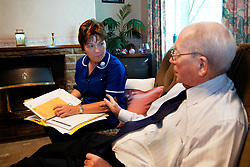 Discharged elderly patient is visited in his home by community nurse Bradford Yorkshire UK