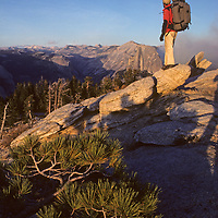 A hiker stands atop Sentinel Dome in California's Yosemite National Park.  Half Dome rises in the background.