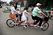 Family riding along on a triple tandem bicycle in Shichahai area, near to Yandai Xiejie and Yinding Bridge, Beijing, China.