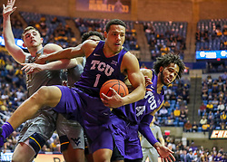 Jan 14, 2020; Morgantown, West Virginia, USA; TCU Horned Frogs guard Desmond Bane (1) grabs a rebound over West Virginia Mountaineers forward Logan Routt (31) during the second half at WVU Coliseum. Mandatory Credit: Ben Queen-USA TODAY Sports