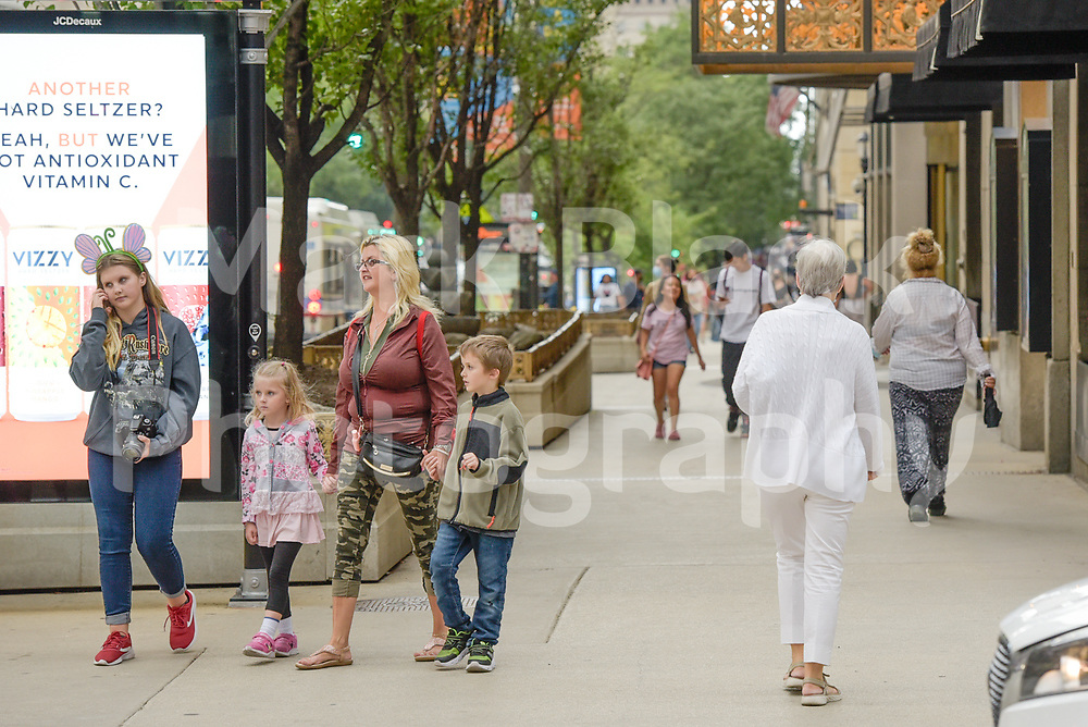 Pedestrians, shoppers and tourist walk along Michigan Avenue in Chicago, Illinois. Photo by Mark Black