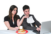 Male and female office workers take a luch break while still at their workstation. Not paying attention to food consuption is a major health and life quality degrader. Woman feeds man while he types on laptop