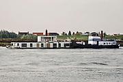 Nederland, Nijmegen, 13-10-2020  Op de Waal vaart een duwcombinatie van een duwschip en een woonboot die naar een andere ligplaats, locatie vervoerd wordt .Foto: ANP/ Hollandse Hoogte/ Flip Franssen