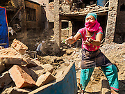 03 MARCH 2017 - BHAKTAPUR, NEPAL: A women recycles bricks from a home in Bhaktapur destroyed in the 2015 Nepal Earthquake. Bhaktapur, a popular tourist destination and one of the most historic cities in Nepal was one of the hardest hit cities in the earthquake. Recovery seems to have barely begun nearly two years after the earthquake of 25 April 2015 that devastated Nepal. In some villages in the Kathmandu valley workers are working by hand to remove ruble and dig out destroyed buildings. About 9,000 people were killed and another 22,000 injured by the earthquake. The epicenter of the earthquake was east of the Gorka district.      PHOTO BY JACK KURTZ