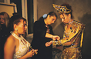 Laetitia gets ready with her third carnival party wedding dress. Laetitia's and Luis's wedding, Baptistes, Ales France. French Gitans, in the south of France, are full of spirit. They live and breathe to the rythmns of rhumba and flamenco music. Any chance to celebrate brings song and dance together with 'palmas' hand clapping. The wedding day is the most important of the brides life, where she moves from a girl to womanhood, where her honesty is tested by the elder women of her clan, with the mouchoir. She will typically have three wedding dresses, white for her religious faith, a special robe of honesty to match the mouchoir, and an over the top carnival outfit. The groom's outfits will match the brides. Thousands will attend a big wedding which can last until almost daybreak.
