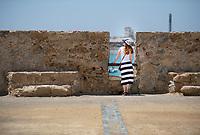 A woman in a striped skirt looks through fort wall near Caleta Beach in Cadiz, Spain,