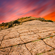 The lines in sandstone in Escalante lead off into a stormy surise in the desert of Utah.