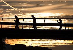 © Licensed to London News Pictures. 13/09/2016. London, UK. People walk to The City across the Millennium bridge on the River Thames at sunrise. Another warm sunny day is expected with hot temperatures predicted in the south east.Photo credit: Peter Macdiarmid/LNP