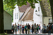 Tourists visiting Beguinage convent - Begijnhof Benedictine monastery / nunnery for nuns in Bruges - Brugge - Belgium