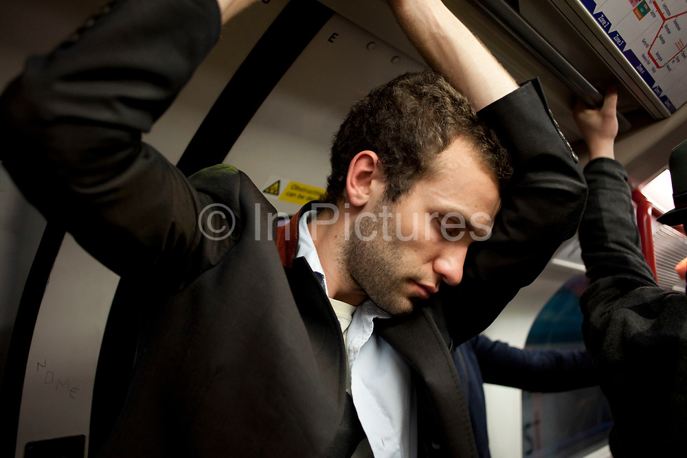 Man sleeping, standing up on an undertground train, London, UK. No doubt tired after a night out and making his way home by public transport.