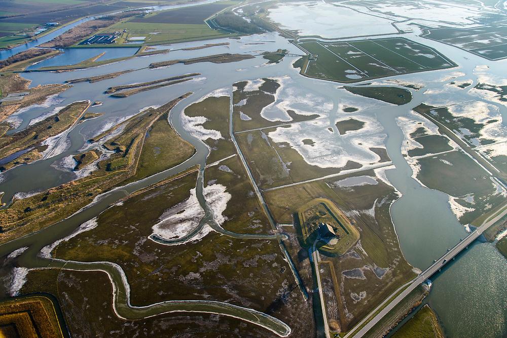 Nederland, Zuid-Holland, Biesbos, 07-02-2018; Polder de Noordwaard in de Biesbosch. In het kader van Ruimte voor de Rivier' (bescherming tegen hoogwater door rivierverruiming) is de dijk van de Merwede gedeeltelijke afgraven en zijn de doorstroomopeningen / inlaten  voorzien van bruggen. Winterse opname met ijs.<br /> Doel is het maken van een doorstroomgebied (naar rechtsboven), bij hoge waterstanden zal het water van de Nieuwe Merwede afgeleid worden en zo westelijk naar het Hollandsch Diep afgevoerd worden. De kans op overstromingen (in de bovenloop) is hierdoor kleiner. Landart from artist Paul de Kort, Growing Moon: depending on the height of the tide, the spiral willl be more or less visible. The art work lies in Polder Noordwaard (part of Biesbosch National Park), part of the program 'Room for the River' (protection against high water by means of creating space for rivers). The former polder can store water and allows the river to flood more easily downstream. These measures dimishes the risk of floods further upstream at high water in the winter.<br /> luchtfoto (toeslag op standard tarieven);<br /> aerial photo (additional fee required);<br /> copyright foto/photo Siebe Swart