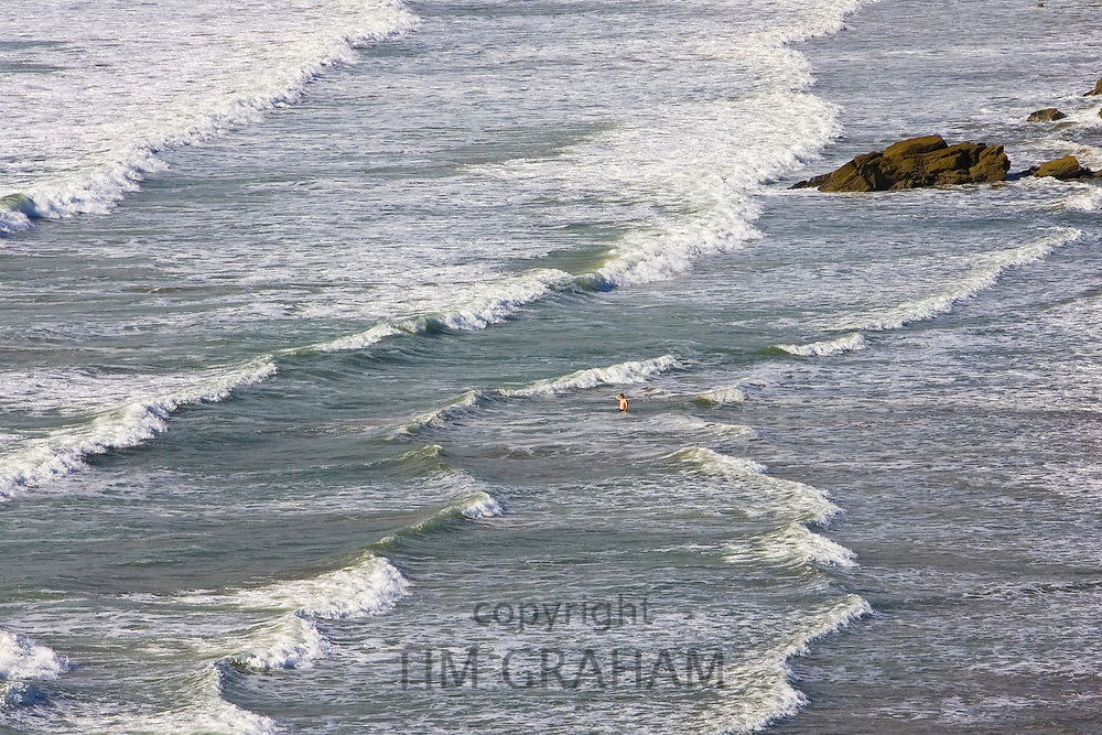 Lone swimmer in the surf at Druidstone Beach near  Broad Haven, Pembrokeshire coast , Wales