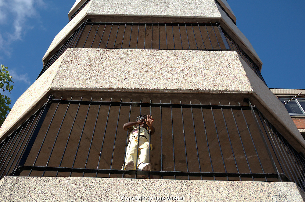 Small child hanging onto railings from balcony of upper floor of highrise flat.