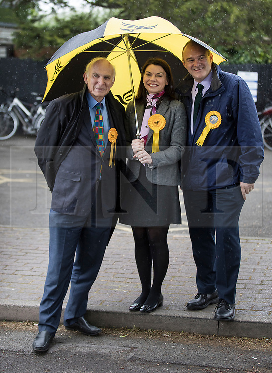 © Licensed to London News Pictures. 01/05/2017. London, UK. Liberal Democrat Parliamentary candidates Vince Cable (L), Sarah Olney and Ed Davey hide from the rain under an umbrella as they wait for party leader Tim Farron - as a day of campaigning begins in Kingston-Upon-Thames. The general election is on June 8th 2017. Photo credit: Peter Macdiarmid/LNP