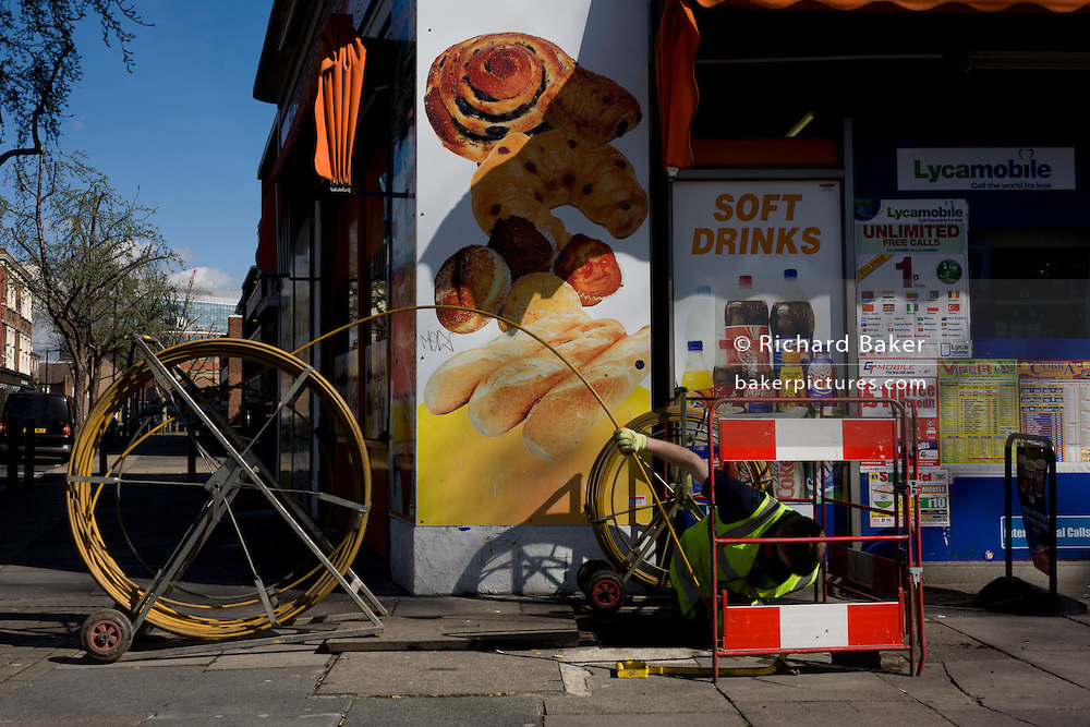 Workman feeds yellow plastic tubing through an under pavement shaft to clear blockage beneath round pastry post ad..