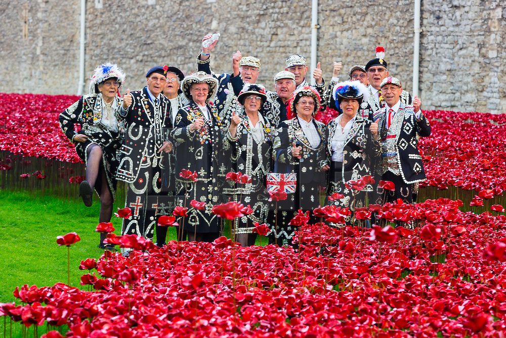 © Licensed to London News Pictures. 19/09/2014. London, UK. Pearly Kings and Queens do the Lambeth Walk as they plant ceramic poppies at The Tower of London's 'Blood Swept Lands and Seas of Red' ceramic poppy installation in central London on 19th September 2014 which commemorates the 100th anniversary of the outbreak of First World War. 'Blood Swept Lands and Seas of Red' is an evolving art installation and 888,246 poppies will be planted in the moat by volunteers, with the last poppy being planted on the 11th November 2014. Each poppy represents a British or Colonial fatality in the First World War. Photo credit : Vickie Flores/LNP