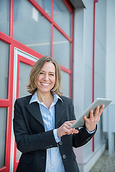 Portrait of businesswoman using digital tablet, smiling