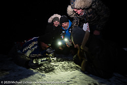 Raphael Bonifay, Simon Pitelet, Frederic Billon and Bertrand Dubet on the frozen lake to make a Baikal Kiss (drill a hole in the ice and fill it with vodka to drink) during the wrap party after the Baikal Mile Ice Speed Festival. Maksimiha, Siberia, Russia. Saturday, February 29, 2020. Photography ©2020 Michael Lichter.