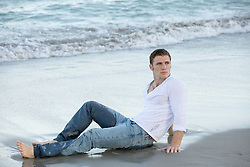man in clothes relaxing on the sand by the ocean in Florida