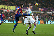 Sam Clucas of Swansea city ®  is challenged by Luka Milivojevic of Crystal Palace. Premier league match, Swansea city v Crystal Palace at the Liberty Stadium in Swansea, South Wales on Saturday 23rd December 2017.<br /> pic by  Andrew Orchard, Andrew Orchard sports photography.