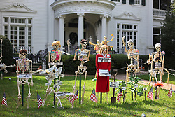 30 October 2015. New Orleans, Louisiana.<br /> The Skeleton Krewe mansion on St Charles Avenue at the corner of State Street draws crowds with its satirically spooky Halloween decorations. American politics comes under fire with skeletons depicting Presidential hopefuls Bobby Jindal, Donald Trump, Marco Rubio, Hillary Clinton and Bernie Sanders depicted as, Bobby Dwindle, Hair Brined Bonehead, Ribio, Secre-terror-y of State, Bush Whacked and Burn-Knee.<br /> Photo©; Charlie Varley/varleypix.com
