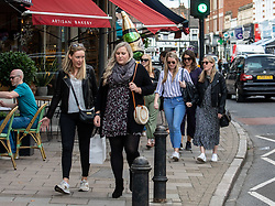 "© Licensed to London News Pictures. 12/09/2020. Surrey, UK. A group of women, one carrying a champagne ballon enjoy the sunshine in Wimbledon Village in South West London this afternoon before the ""Rule of 6"" comes into force on Monday as weather experts announce a 6 day mini heatwave in the South East of England this week with highs in excess of 29c. Prime Minister Boris Johnson is already under pressure after he announced on Friday that gatherings of more than six people will be banned from Monday in the hope of reducing the coronavirus R number. The Rule of Six as it is known, has already become unpopular with MPs and large families. Photo credit: Alex Lentati/LNP"