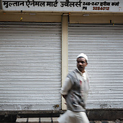 Man walking past closed shop in Chandni Chowk, Old Delhi