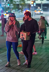 "© Licensed to London News Pictures; 25/09/2020; Bristol, UK. People carry takeaway alcohol after 10pm in the city centre which is much quieter than usual for a Friday night, on the first weekend of the 10pm early closing curfew for pubs, bars and restaurants across the UK, imposed by the government to try and halt a second wave of the covid-19 coronavirus pandemic. Gathering in groups of more than six people is also banned and there are penalties of £200 on the first offence. From Monday 14 September it was illegal to meet up socially in groups of more than six people, known as the ""Rule of Six"", in order to try and contain the spread of the covid-19 coronavirus pandemic. Photo credit: Simon Chapman/LNP."