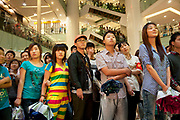 Crowds of shoppers watch a massive PR promotional push by cell phone company Mororola. Following a stage presentation with models and large screens, the mobile phone giant has staff selling phones to customers as well as fun and giving away gifts by way of mass marketing. Crowds gathered to watch and buy. Xidan is one of the main commercial shopping area in the Xicheng district of Beijing, China. With Joy City as it's centerpiece, a 13-story coplex of western and Chinese shops. This is a shoppers haven as modern consumerism and commerce have a strong grip on Beijing's shop hungry crowds.