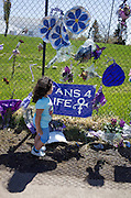 Young child visits Prince memorial with purple posters, balloons and bouquets. Paisley Park Studios Chanhassen Minnesota MN USA
