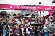 London 2012 Olympic Park in Stratford, East London. Crowds of people stream over the walkway from the Westfield Shopping Centre towards Stratford transport hub.