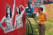 Glastonbury Festival, 2015. Shangri La is a festival of contemporary performing arts held each year within Glastonbury Festival. The theme for the 2015 Shangri La was Protest. Woman designing the site standing in front of  Women's lib poster.