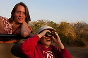 "Rebecca Shooter with Tyler Talmage on the safari land cruiser in the Phinda Game Reserve, South Africa.<br /> <br /> Phinda Private Game Reserve encompasses an impressive 23 000 hectares (56 800 acres) of prime conservation land wilderness in KwaZulu-Natal, South Africa. Showcasing one of the continent's finest game viewing experiences. Phinda is described as ""Seven Worlds of Wonder"", with its seven distinct habitats - a magnificent tapestry of woodland, grassland, wetland and forest, interspersed with mountain ranges, river courses, marshes and pans. Phinda is a wilderness sanctuary where intimate encounters, adventure and rare discoveries can be experienced firsthand."