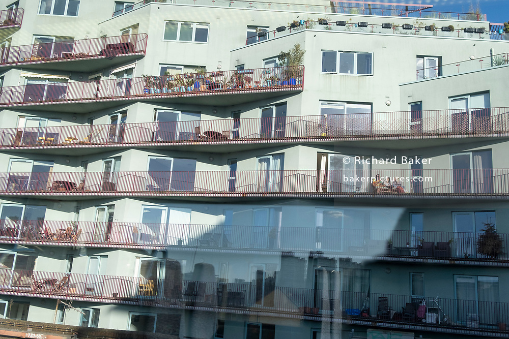 Residents of members of the same social bubble sit in sunshine, on a balcony of a block of new apartments in Camberwell during the third lockdown of the Coronavirus pandemic, on 26th February 2021, in London, England.