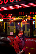 A young commuter woman awaits her bus on a southbound route at a stop on Charing Cross Road in central London. Surrounded by red hues from the bus behind the girl and from lettering from an Angus Steakhouse restaurant, the female is also in a red coat on this November night. She is of Chinese ancestry, a Sino-British family moved to the UK whose spiritual home is nearby Chinatown, across the road. She looks wistful, deep in thought about her homeward journey, while surrounded by the bustle of the capital.