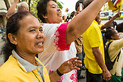 05 DECEMBER 2012 - BANGKOK, THAILAND:  A woman reacts to seeing the motorcade of Bhumibol Adulyadej, the King of Thailand, pass her position Ratchadamnoen Avenue in Bangkok, Wednesday. December 5 is a national holiday in Thailand. It's also celebrated as Father's Day. Celebrations are being held across the country to mark the birthday of Bhumibol Adulyadej, the King of Thailand.   PHOTO BY JACK KURTZ