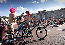 © Licensed to London News Pictures. 14/08/2021. London, UK. A couple pause for photographs as they pass Buckingham Palace during the World Naked Bike Ride in central London. Activists are protesting against the global dependency on oil and are calling for an end to the car culture. Photo credit: Peter Macdiarmid/LNP