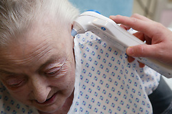 Elderly woman having her temperature checked,