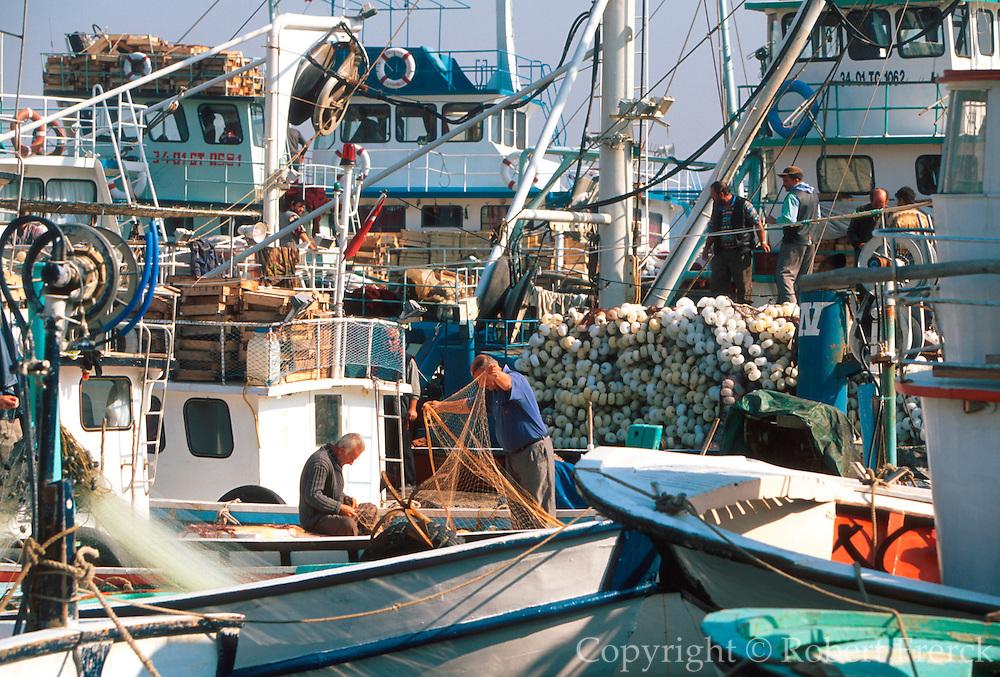 TURKEY, ISTANBUL, BOSPHORUS Fishermen repair nets on boats in the tiny harbor of the fishing village of Sariyer on the European shore
