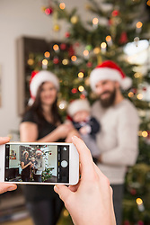Woman using phone to photograph family