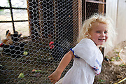 Anna Bell, three year old daughter of farm owners Dave and Jill Bell, proudly shows off the family's chicken coop at Bell Organic Gardens in Draper Utah.